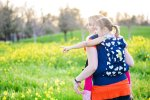 mom and child standing in a field of mustard