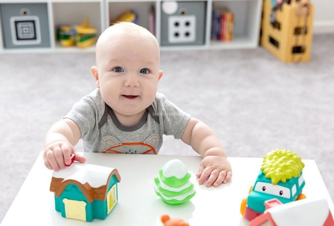 baby in fox onesie playing with toys