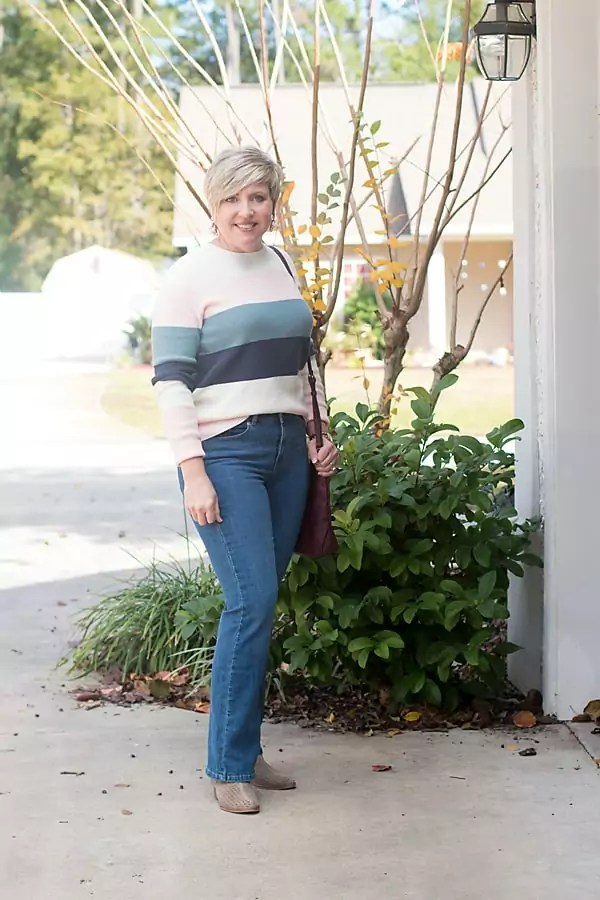Fashion blogger in boot cuts Levis jeans and colorblock sweater.
