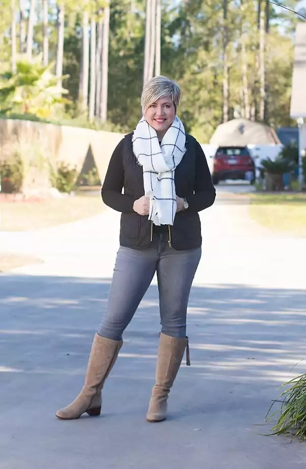 Over 40 fashion blogger in winter outfit featuring grey jeans, black sweater, black vest and tan boots.