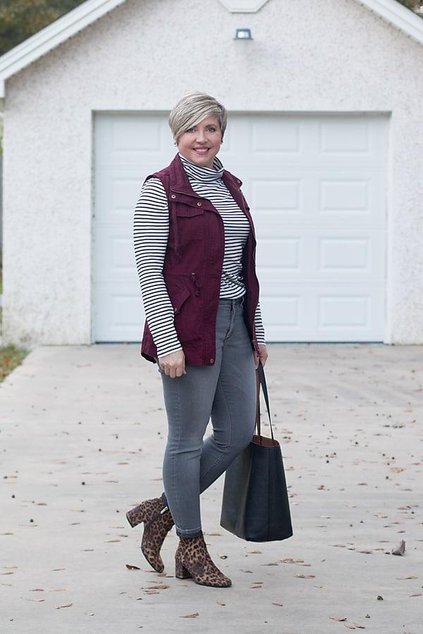 Fashion blogger in JCrew turtleneck tee, burgundy utility vest, and grey NYDJ jeans.