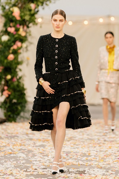 A black evening dress with golden details, a design inspired by a Chanel tweed suit