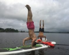 men doing yoga pose in paddle boards