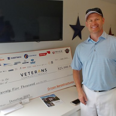 Scott Schroepfer with the check being donated to the Vetrans Community Project