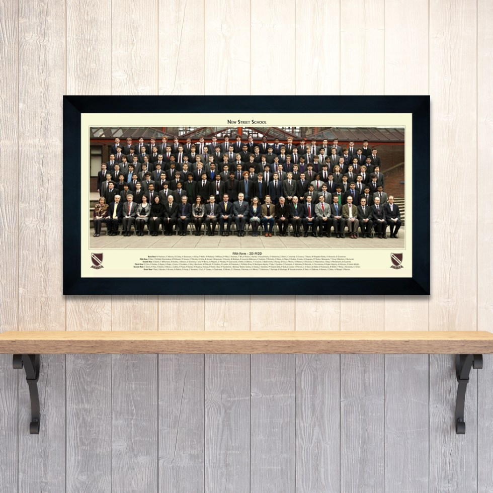 Large school year group photograph presented in a black frame and hung on a wall above a wooden shelf
