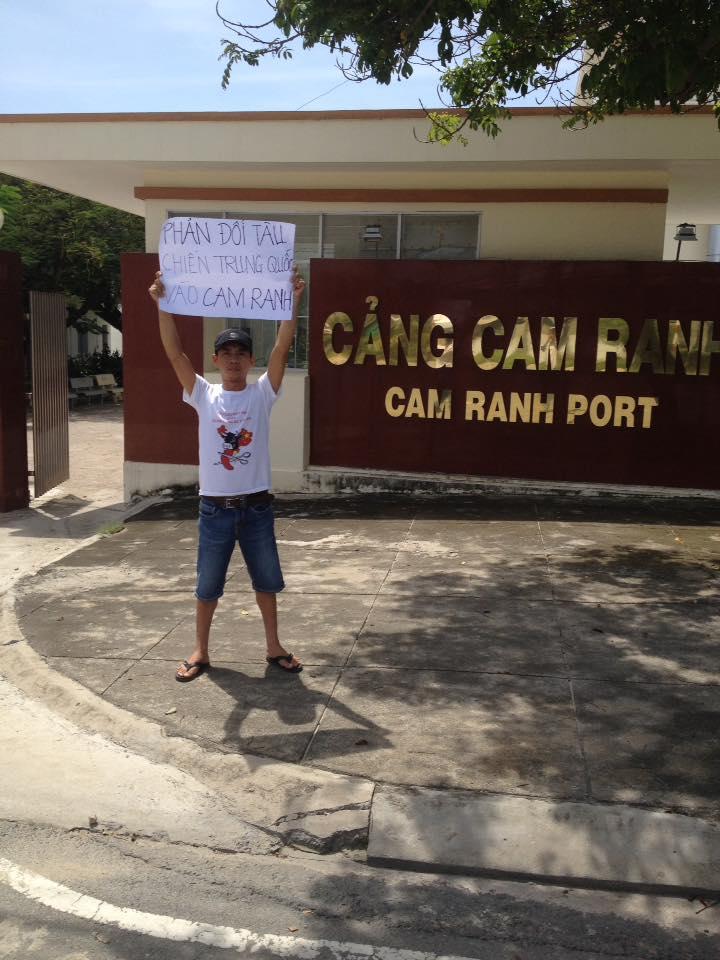 Anh Vũ Đạt Phong giăng biểu ngữ trước cảng kinh tế Cam Ranh sáng ngày 22/10. Ảnh: Facebook Vũ Phong