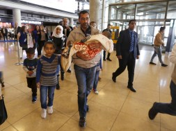 Syrian refugee Ahmad al Aboud and his family members walk to board their plane at the Queen Alia International Airport in Amman