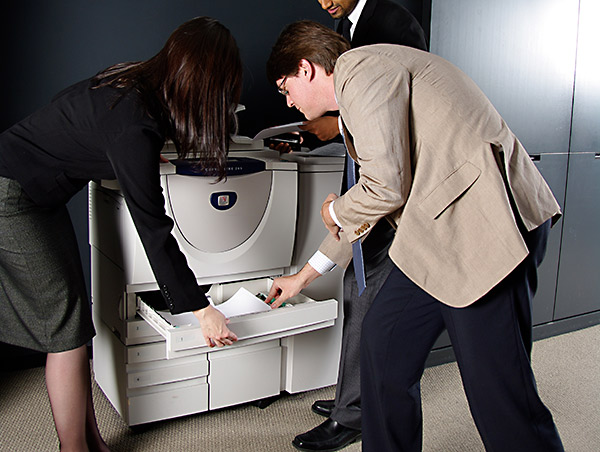 people trying to use a printer together.