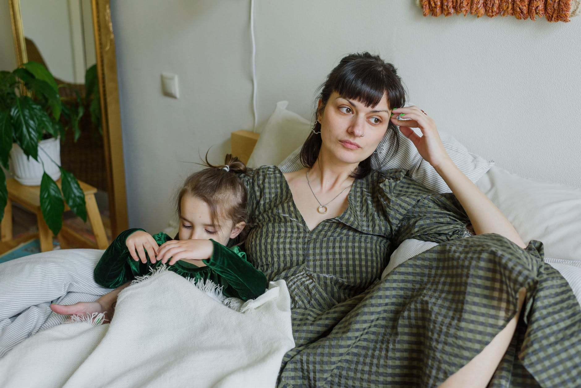 tired mother with cute daughter resting on bed in cozy room