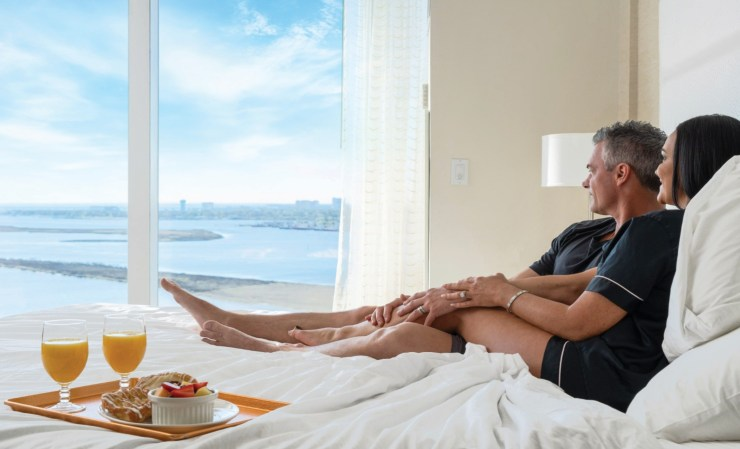 Couple laying in bed with room service
