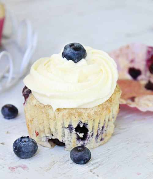cupcake with white icing and blueberries
