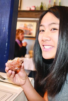 """Lara Kong enjoys her """"appetizer"""", a sweet and savory bacon apple fritter. (Photo by Emma Williams)"""