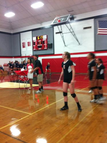 Junior Jenny Kerbs waits for coaches Jason Kreps and Sarah Song to throw a volleyball to hit in their pre-game practice.