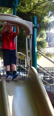 Caden Millsback prepares to slide down a slide.