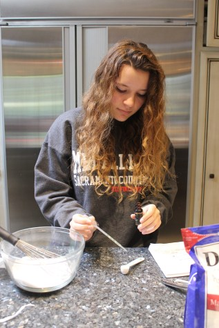 Senior Aidan Galati measures an essential oil, the ingredient that gives her bath bombs their scent, prior to mixing it with epsom salts.