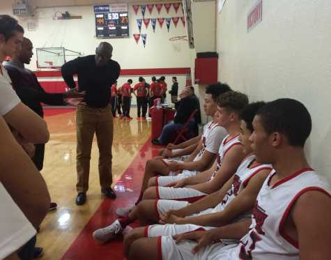 Coaches Gary Brisco and David Ancrum talk to the varsity boys during a timeout.