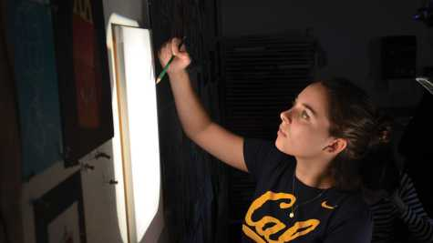Senior Emma Brown traces her self portrait onto a blank campus during studio art.
