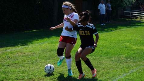 Freshman Abby LaComb fights for the ball against a Delta defender in the girls' May 12 playoff game.