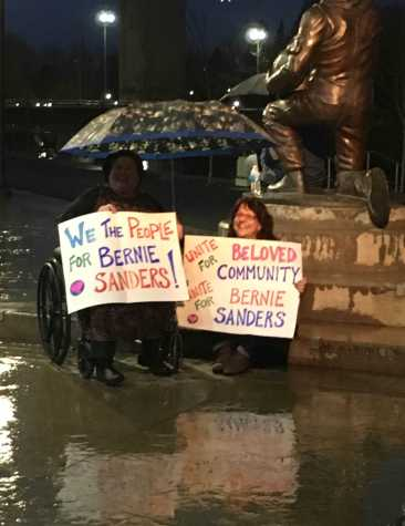 Fans hold up their signs in support of Sanders.
