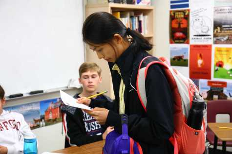 Junior Zihao Sui reads the propositions on a mock election ballot.