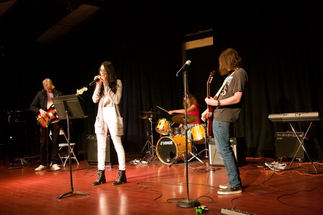 "The ""old"" Garage Band – consisting of bass guitarist Aaron Graves, a senior; lead singer Téa Huynh Van, a senior; drummer Allie Bogetich, a junior; and guitarist Max Kemnitz, a senior – perform ""Hysteria"" by Muse and ""Reptilia"" by The Strokes. (Photo by Shimin Zhang)"