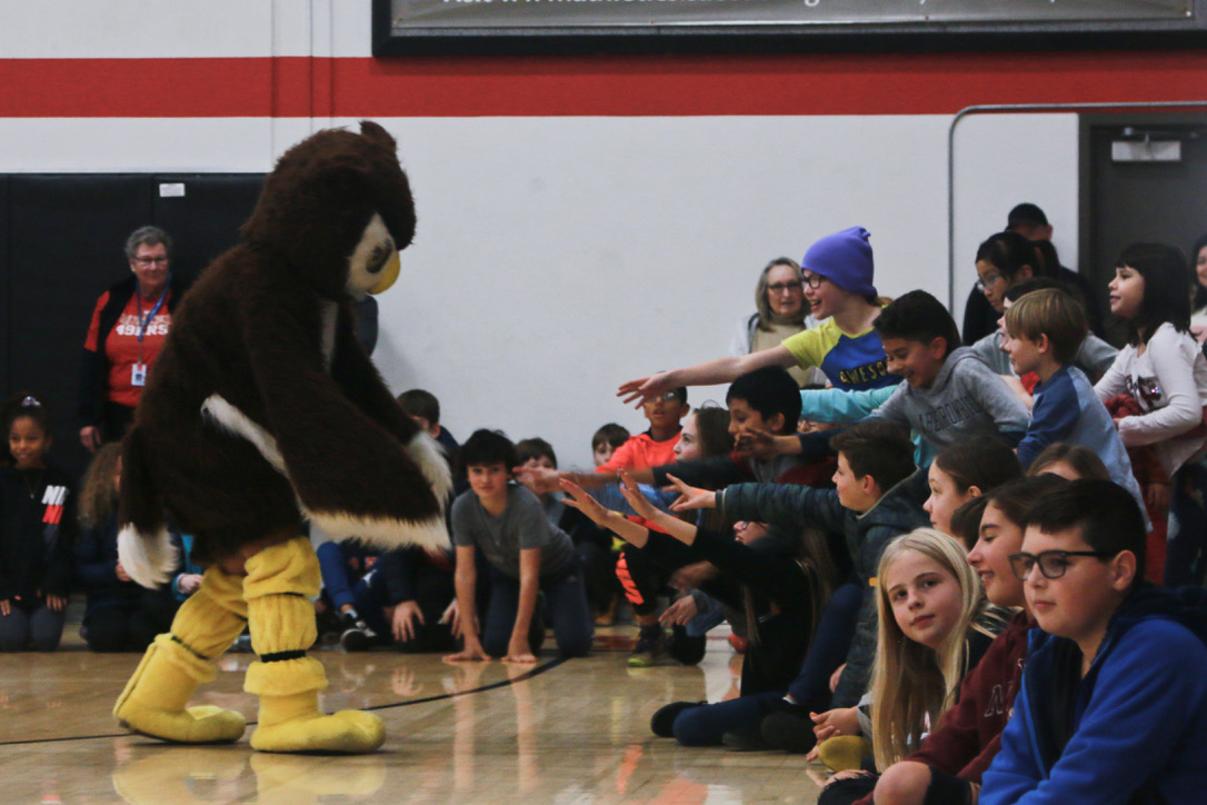 During the pep rally, Baxter the Owl runs to high-five students.