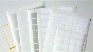 Mehrere weiße Etiketten auf Bogen liegen aufeinander