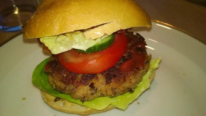 Der fertige Kidneyburger mit Semmel, Salat, Tomate und Gurke