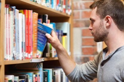 Male student picking an Inbound Marketing book in a library for reading and researching