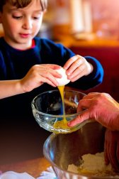 A boy cracks an egg into a glass bowl being held up by a parent.