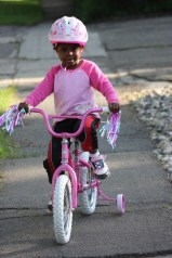A little girl rides a pink bicycle down the sidewalk.
