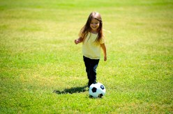 A little girl plays with a soccer ball on a field of grass.