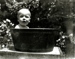 Rasmussen family baby sitting in an outdoor washtub.