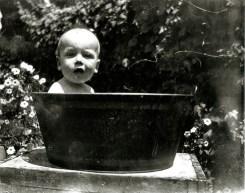 Rasmussen family baby sitting in an outdoor washtub.