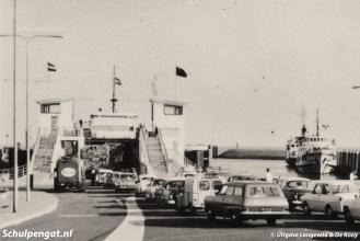 De veerhaven van 't Horntje was een drukte van belang in 1964. Auto's rijden hier de nieuwe aanlegsteiger op voor de Marsdiep, rechts zien we de veerstoep voor zijladers.