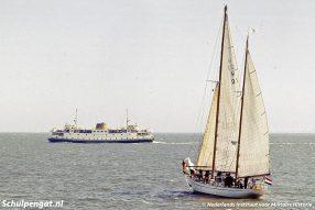 Het opleidingsschip Hr.Ms. Urania vaart op het Marsdiep met op de achtergrond de veerboot Marsdiep (1964).
