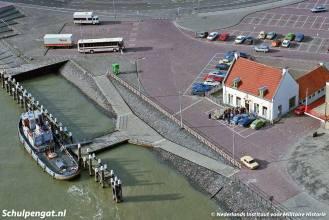 Een luchtfoto uit 1983 van de zijladingssteiger van Den Helder met links nog een stukje van de veerstoep. Aan de voormalige TESO-steiger ligt een sleepboot van de Koninklijke Marine.