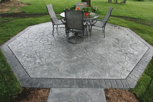 Patio in Random Stone with Lt.Gray color hardner and Dk. Gray antique. Brick stamped border in Charcoal