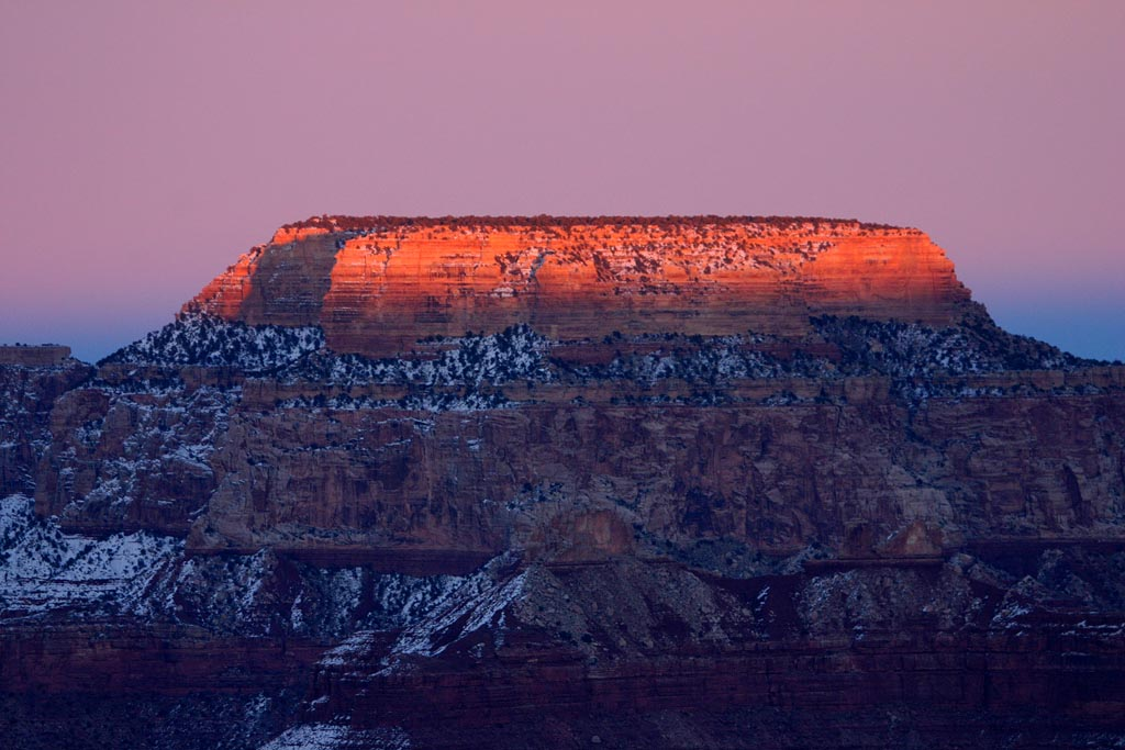 Mesa of sedimentary rock coloured by sunset