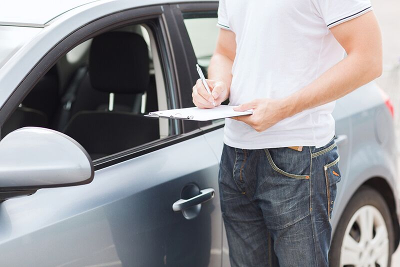 man signing paperwork on his car