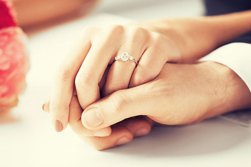 couple holding hands and showing off engagement ring