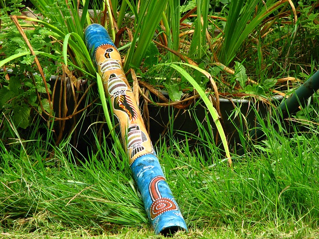 A colourfully painted didgeridoo lying in grass