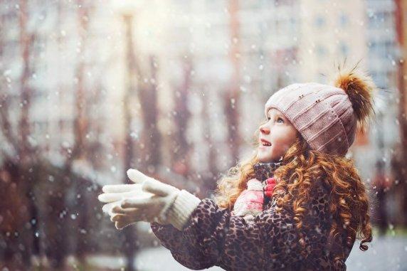 A linda garotinha estica a mão para pegar flocos de neve caindo.  Primeira neve.  Filtro instagram tonificante.