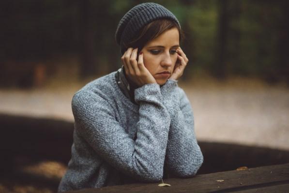 Retrato de mulher triste e deprimida, sentado sozinho na floresta.  Conceito de solidão ou depressão (Wstockstudio) s