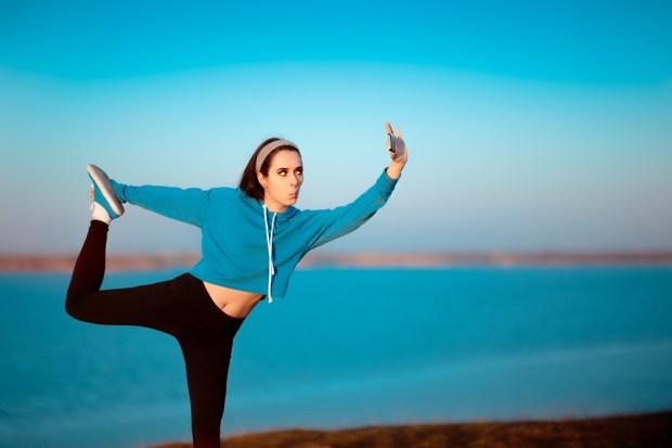 Garota em pose de ioga, tirando uma selfie fora na natureza (Nicoleta Ionescu) s