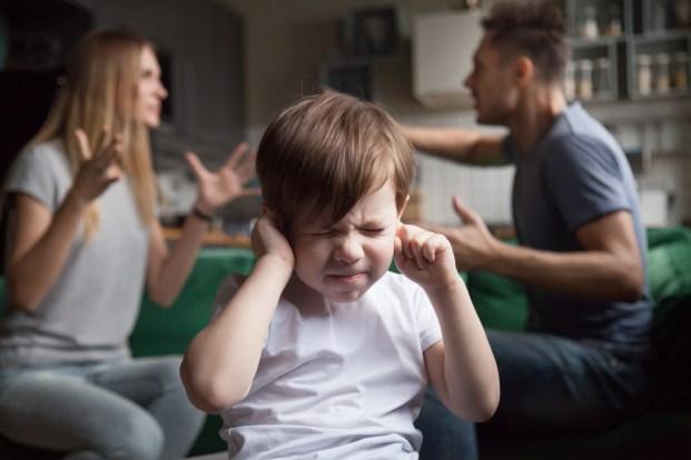 Filho de criança frustrada coloca os dedos nos ouvidos, sem ouvir pais barulhentos discutindo (fizkes) s