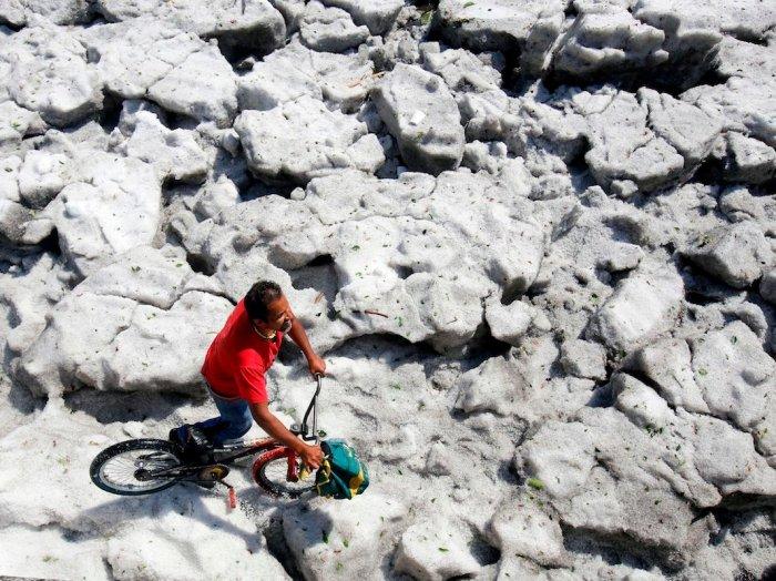 A man walks his bike on a sheet of ice on Sunday. (Ulises Ruiz/AFP/Getty)