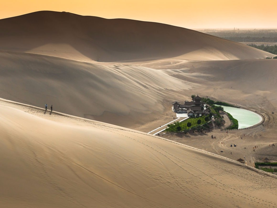 the-crescent-lake-or-yueyaquan-in-chinese-is-a-fresh-water-spring-in-the-shape-of-a-half-moon-that-sits-in-the-gobi-desert-the-oasis-is-believed-to-have-existed-for-around-2000-years-though-it-has-seen-its-water-levels-decline-and-attractio