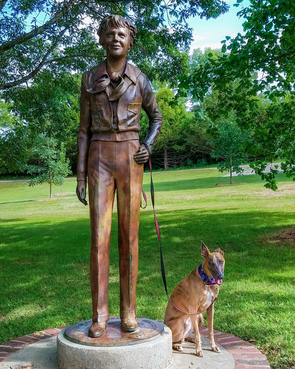 Kuiper poses with a statue of Amelia Earhart. She is holding his leash.