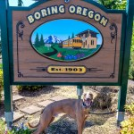 "Kuiper smiles proudly in front of the ""Welcome to Boring, Oregon"" sign."